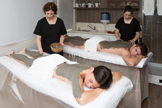 Beautician applying clay mask on legs of woman and man