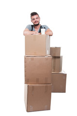 Mover man having coffee on cardboard boxes