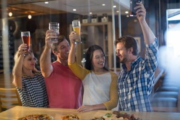 Cheerful friends holding beer glass in bar