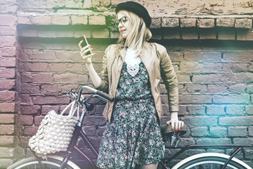 City lifestyle stylish hipster girl with bike using phone texting on smartphone app in street