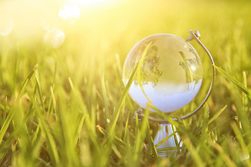 low angle of small crystal globe in the grass. travel and global concept