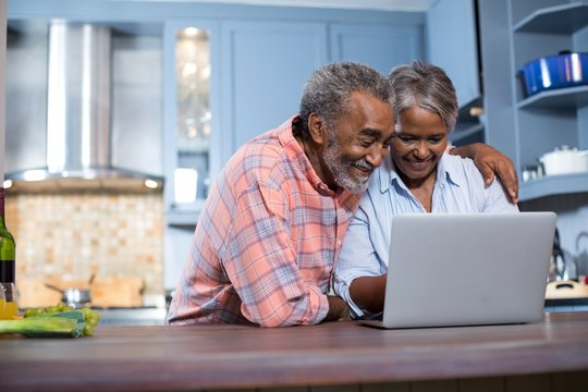 Smiling couple using laptop computer