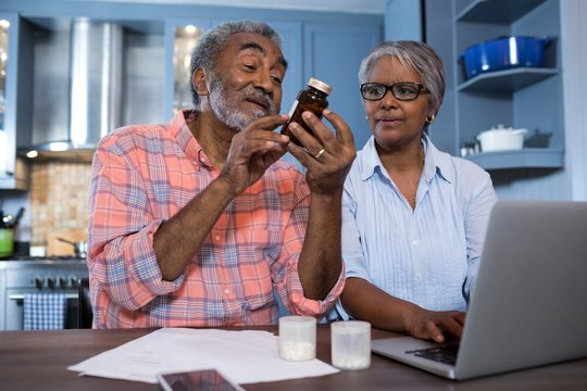 Man looking at medicine while sitting by woman using laptop