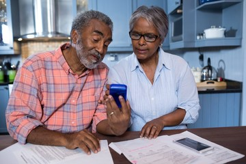 Couple using calculator in kitchen