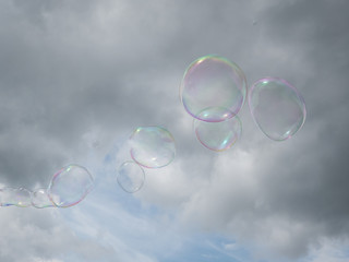 Colorful soap bubbles in front of a cloudy blue sky