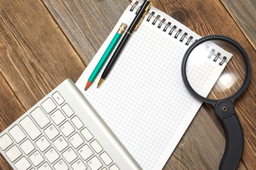 notebook, computer keyboard, magnifying glass and a pencil with a ballpoint pen