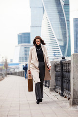 Smiling dark-haired woman in a bright coat is on the waterfront