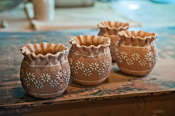 Pottery production. How to make clay products, jugs, pots, vases. Clay workshop. Painting and molding of clay products Shelving with clay products