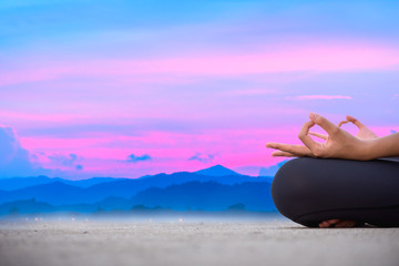 Healthy woman doing Yoga Meditation exercise on the beach behind colourful sunset sky.