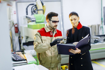 Pretty young woman controlling process in the factory