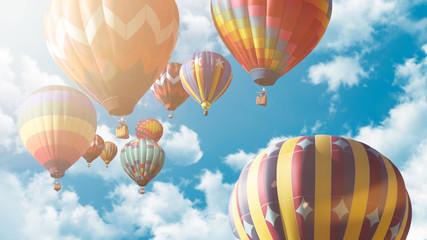 Mehrere Heißluftballons fliegen vor einem blauen bewölkten Himmel bei Sonnenuntergang