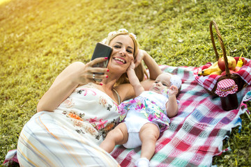Young mother taking a selfie photo while baby girl touching mother's face. Happy moments, picnic, motherhood concept.