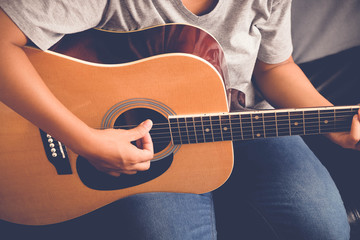 woman's hands playing acoustic guitar with filter effect retro vintage style