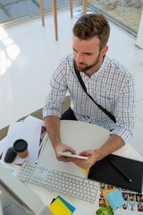 High angle view of graphic designer using tablet computer at desk
