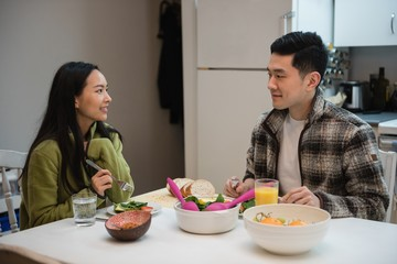 Couple interacting while having breakfast in kitchen