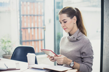 Young woman using tablet  in modern place. Business people with relaxing emotion at modern office. Greeting deal concept
