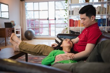 Couple interacting while relaxing on sofa in living room