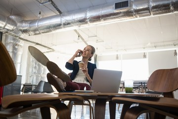 Businesswoman talking on smart phone while relaxing in office