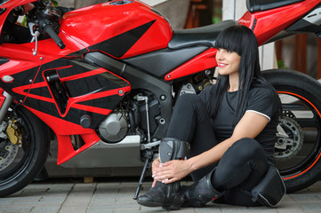 Freedom and style. Bright portrait of a young woman with a red motorcycle. Girl biker sits in front of a motorcycle