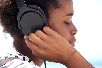 Close up young african american female listening music on headphone