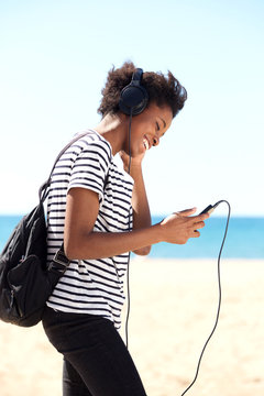 Young woman listening to music from mobile phone outside