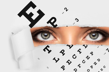 Woman looking throug torned papaer with eye chart
