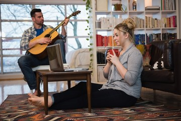 Woman having coffee while man playing guitar in living woman