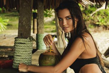 Happy woman is enjoying coconut drink in the beach bar