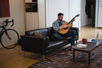 Man playing guitar while relaxing on sofa in living room