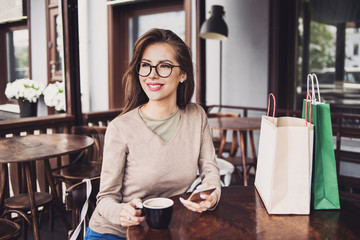 Beautiful young woman with shopping bags using her smart phone. Cute girl drinking coffee at cafe after shopping