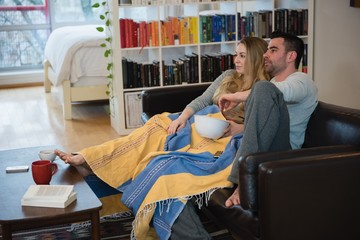 Couple having popcorn while relaxing on sofa in living room
