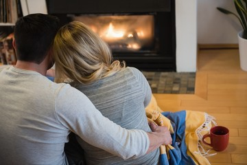 Rear view of couple relaxing in living room