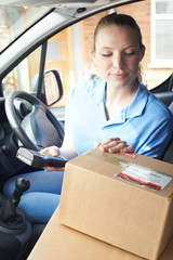 Female Courier In Van Delivering Package To Domestic House