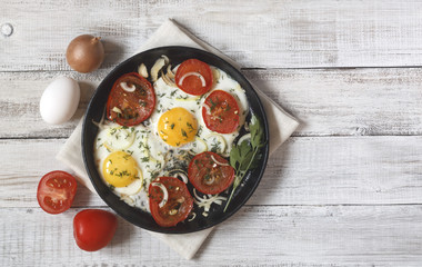 Keuken foto achterwand Gebakken Eieren Fried eggs with vegetables and greens (tomatoes, onion, dill) on wooden background on a linen napkin with copy space for your text.