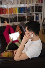 Man talking on mobile phone while woman using digital tablet on sofa