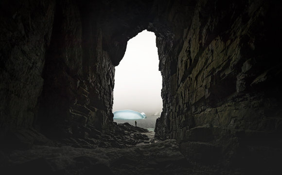 The man stands at the end of the cave in the background of the glaciers. Andreev.