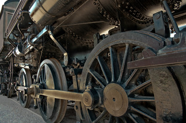 Locomotive:  A large boiler rests on the heavy iron wheels of an old steam locomotive.