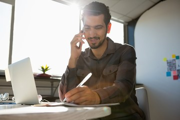 Man talking on phone at desk in office