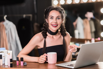 Excited girl using computer in dressing room