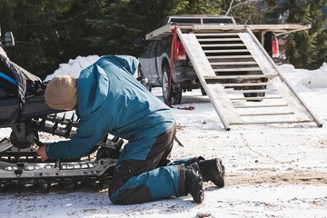 Man repairing snowmobile on a sunny day