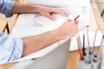 Youthful man making picture of manufacture on paper at workplace