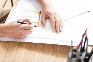 Young craftsman doing design of new furniture at workplace