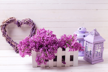 Lilac flowers in box, decorative lanterns and heart on white wooden background.