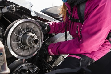 Mid-section of woman repairing snowmobile