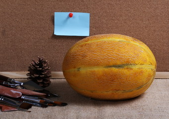 Yellow melon, paint brushes and blank notice board with pinned sticky note on jute, linen sack