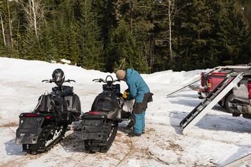 Man filling gas tank of snowmobile