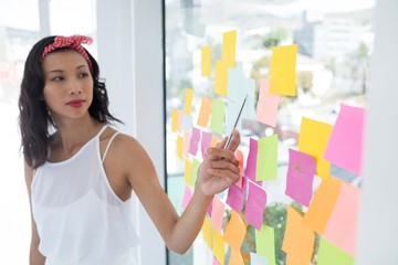 Female executive pointing at sticky note in office