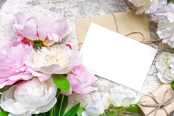 blank white greeting card and envelope with gift box in frame of peonies and roses flowers