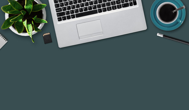 Office desktop with notebook, flash drive, mug of coffee, pencil, flower and blank sheet. Top view of office table with electronic gadget and stationary for work. Work, technology and business concept