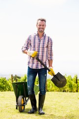 Portrait of young man holding shovel by wheelbarrow